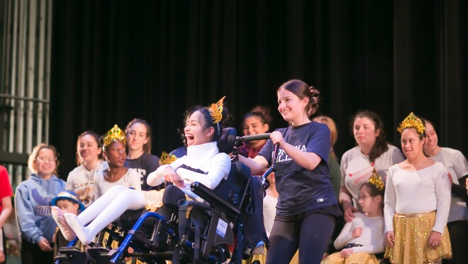 A dancer wearing a tiara sits in a wheelchair. A teen girl stands behind the wheelchair and assists with the performance. Other dancers and helpers are in the background.