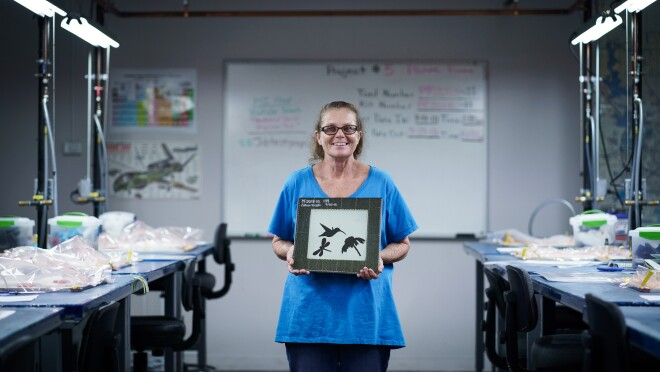 A woman in a blue T-shirt holds a framed craft project depicting a hummingbird, a dragonfly, and a flower.