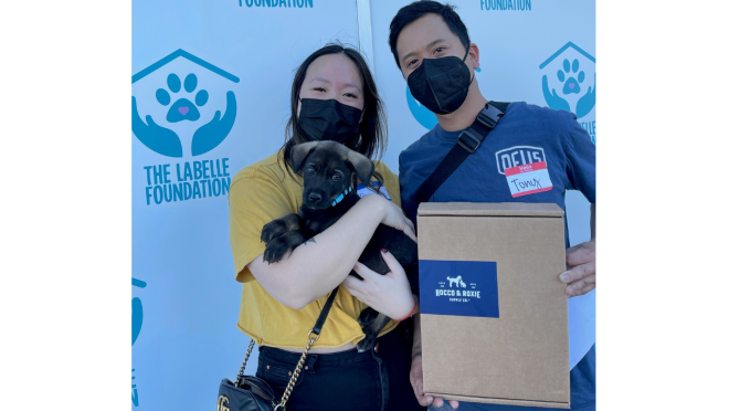 Two people pose for a picture with their new puppy. One of them is holding a Rocco & Roxie box while the other holds the black and brown puppy close.
