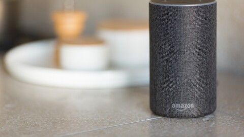 A grey Amazon Echo device sits on a counter.