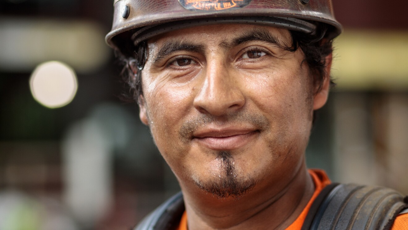 A man in construction helmet and orange safety jacket is photographed at a construction site on Amazon's campus in Seattle, WA. He is smiling at the camera.