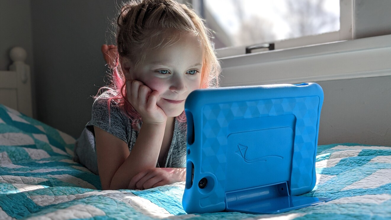 A young girl lays on her stomach in bed and smiles as she watches her Fire Tablet.