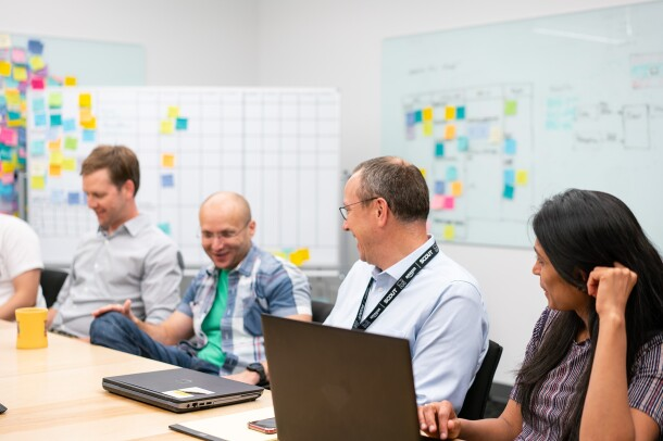 Amazon Scout hardware engineers sit together at a conference table, having a discussion.