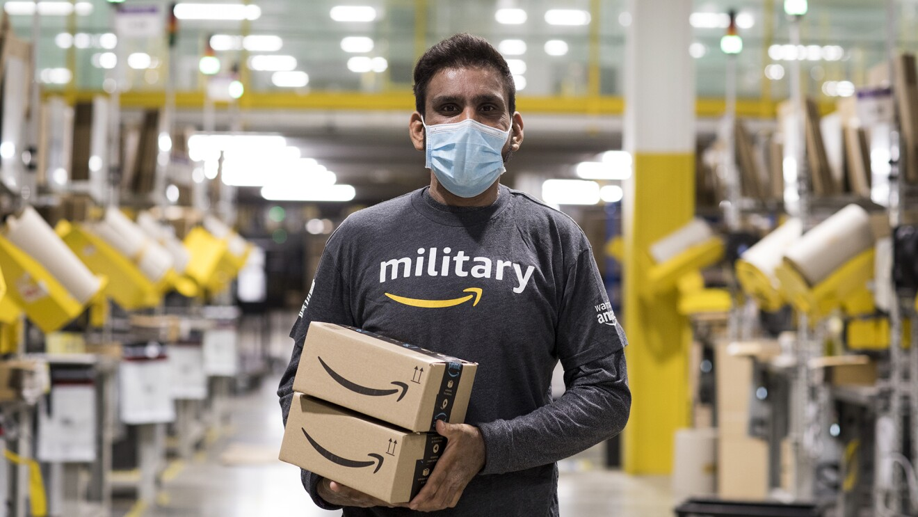"""An image of an Amazon employee working at Amazon while wearing a shirt that says """"military"""" with the Amazon logo under it."""