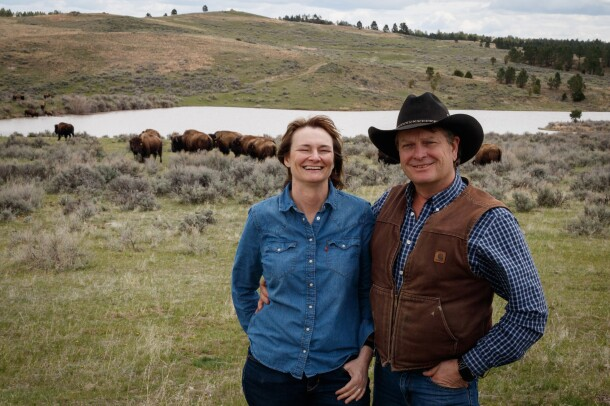 A woman and a man in a cowboy hat stand in a pasture on a ranch in Wyoming with grazing buffalo in the background.