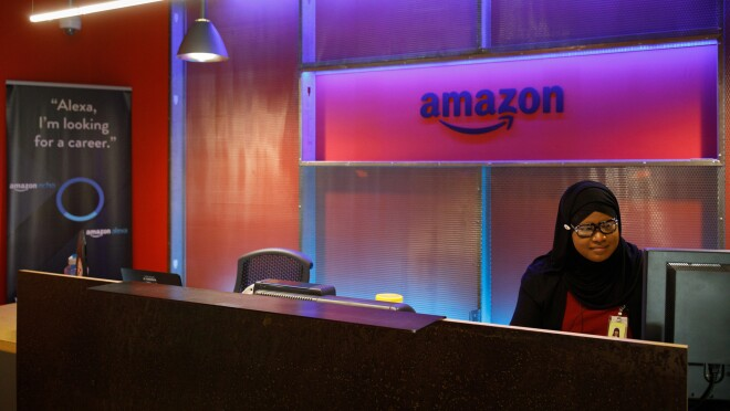 """The reception area of Amazon's Pittsburgh, PA office. There is purple accent coloring and a woman sits at a computer. The sign to the left says """"Alexa, I'm looking for a career."""""""