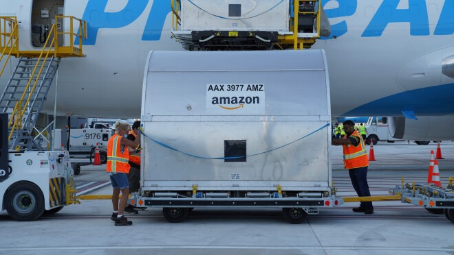 An image of a large metal container being loaded onto a Prime Air plane.