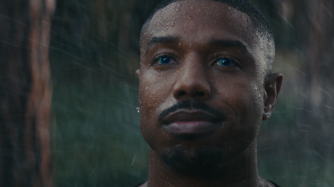 Michael B. Jordan has droplets of water on his face, and the background looks to be outdoors, with driving rain. His eyes have a blue hue to them.