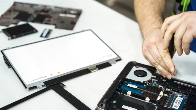 The photo shows a disassembled laptop computer. Parts of the computer and its casing are in the left section of the image. To the right, a pair of hands are poised over the opened up computer. The person working on the computer is holding a screwdriver.