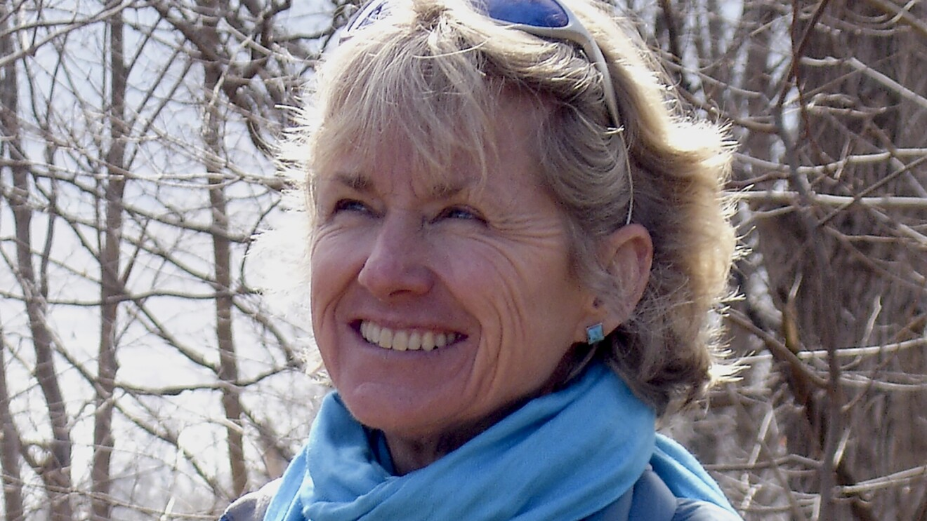 Amazon author Kristiana Gregory, a woman with blond hair, smiles looking to the left. She is wearing a blue scarf and blue square earrings. It's winter, and trees with no leaves are in the background. She has sunglasses on her head.