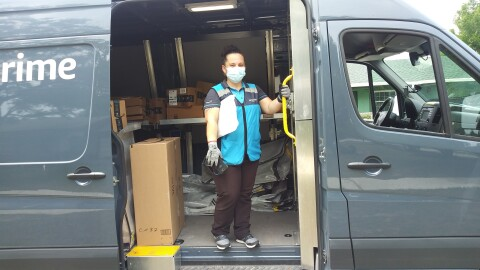 A woman delivery driver wearing a mask stands inside an Amazon van, preparing to deliver customer packages.