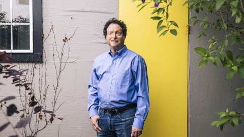 Josh Miele, Principle Accessibility Researcher at Amazon Lab126, stands for a portrait at his home in Berkeley, California. He is standing outside of his home in front of a light gray wall with a small window and a bright yellow door. There is a small tree and a small plant on either side of him.