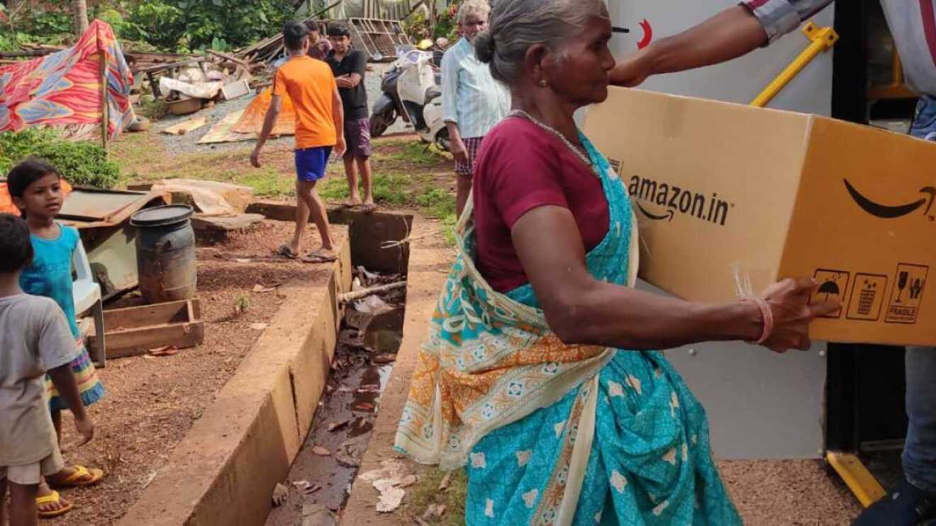 An old woman receiving Disaster Relief package from amazon india