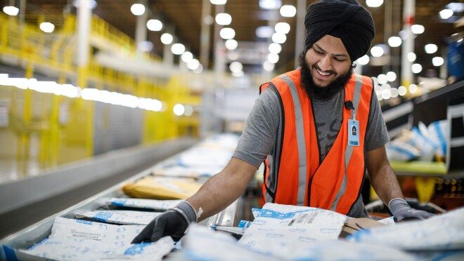 An Amazon associate wearing safety gloves and vest over his clothes, handles customer orders at an Amazon Fulfillment Center, BFI5 in Kent, Washington.