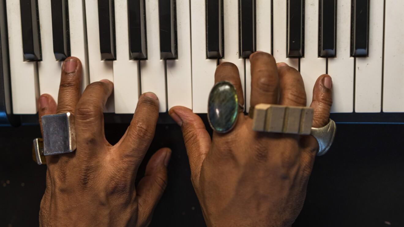 A person wearing rings plays music on a small keyboard.