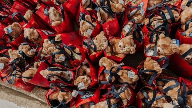 An image of red bags that have teddy bears and other fun items in them for donation.