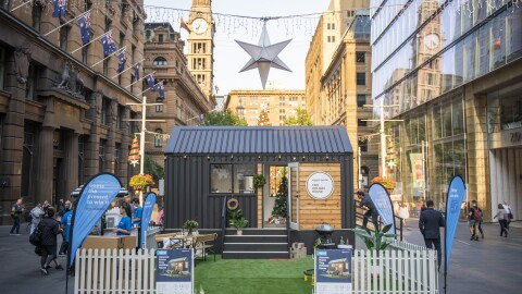 A tiny house set up in a city street for display.