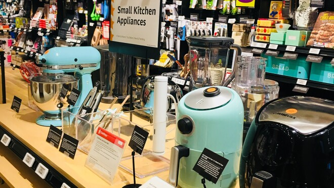 """A display area in Amazon 4-star. A display area of Small Kitchen Appliances has a KitchenAid Mixer, Sous Vide, air fryer, food processor and more. Behind the display are sections for """"Cooks' Tools,"""" """"Kitchen Gifts,"""" """"Bar and Party Supplies,"""" """"Quirkly Kitchen Gifts,"""" and more."""