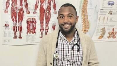 Shaquille Robinson, an injury prevention specialist at Amazon, stands in front of a wall with posters of human muscular anatomy. He is looking at the camera and wearing a stethoscope around his neck.