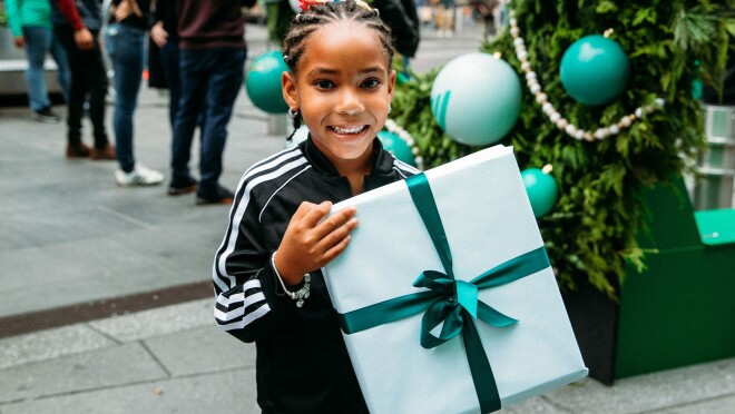 An image of a young girl smiling for a photo while holding a wrapped present. There is a restive wreath in the background of the photo.