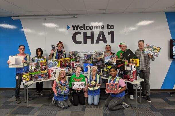 Amazon associates pose with toys raised for Ronald McDonald House