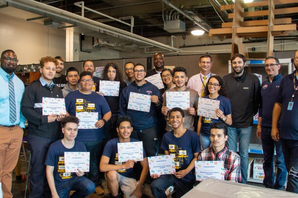 Several students gather together in a group at a high school. They hold up Amazon Future Engineer certificate, and are flanked by teachers.