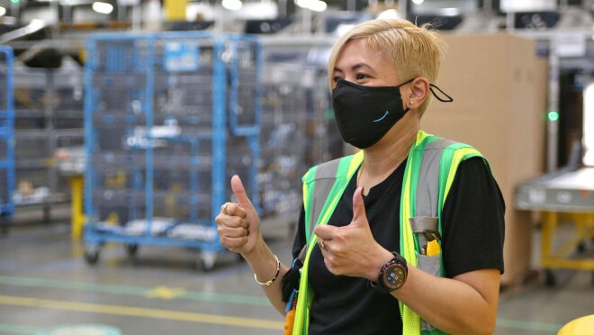 A woman wearing a face mask and a safety vest gives two thumbs up to someone off-camera. She is standing in an Amazon fulfillment center.