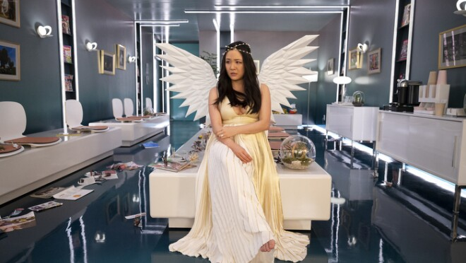 An image of Constance Wu sitting on a table in a clinical waiting room. She is wearing a long, white dress, angel wings, and a small, gold crown.