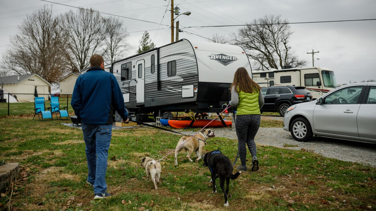 A man, a woman, and three leashed dogs walk toward a parked RV.
