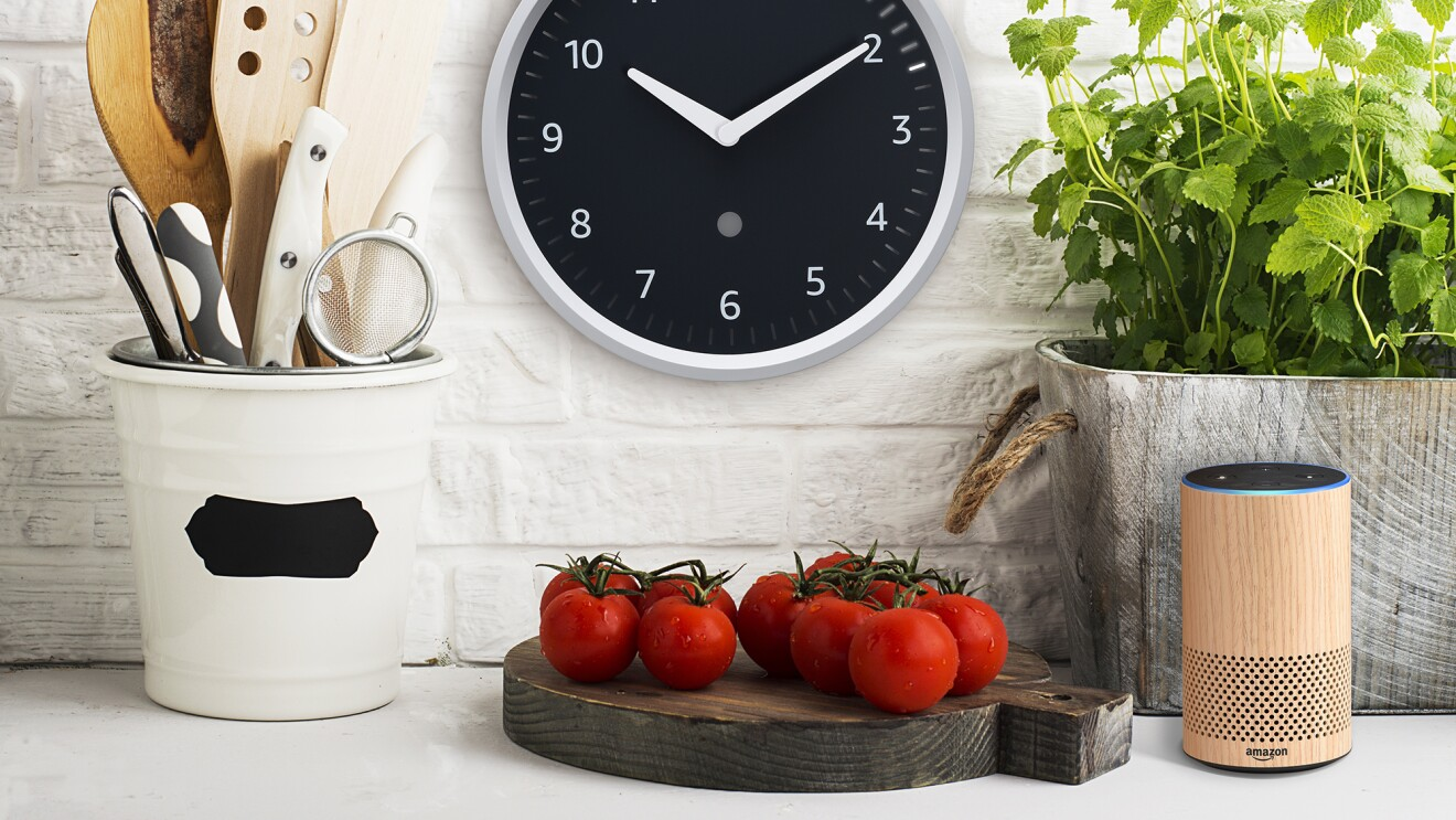 Amazon Echo Clock on the wall in a kitchen. To the left is a carafe of kitchen tools, below the clock is a cutting board with tomatoes. To the right, an herb growing in a container, and an Echo device.