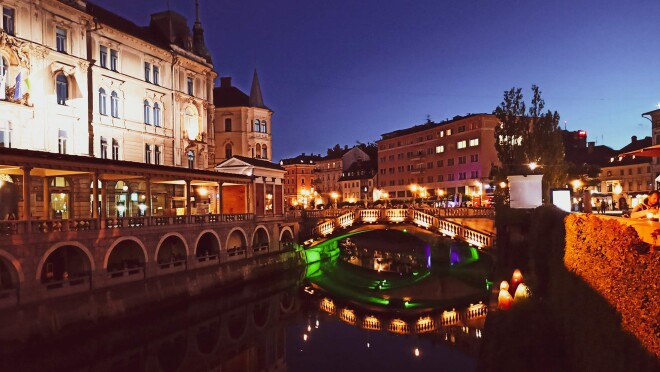 An image of a Slovenian city at night. There is a bridge over a canal with lights illuminating the bridge and surrounding buildings.