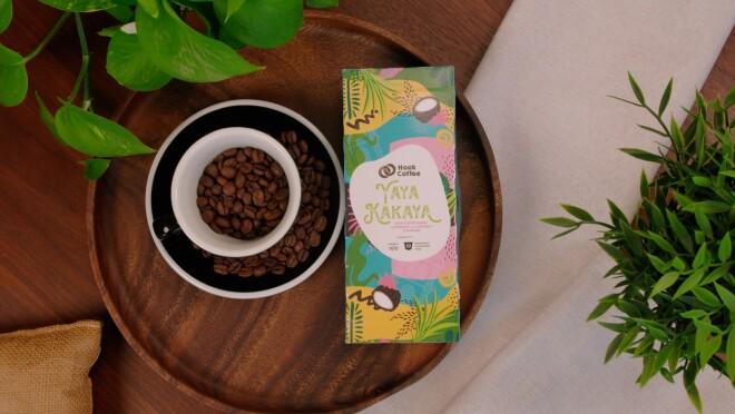 Yaya Kakaya placed beside a cup of coffee beans