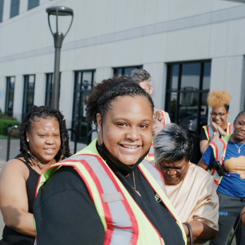 A woman wearing a safety vest smiles at the camera, as her friends and family gather behind her.