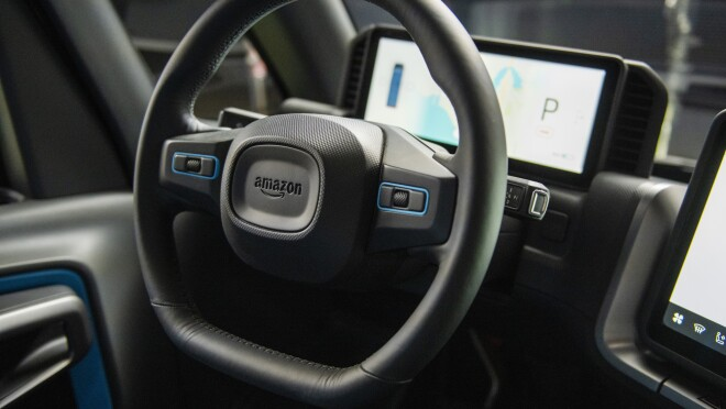 A steering wheel with the Amazon logo includes built-in microphones and speakers.
