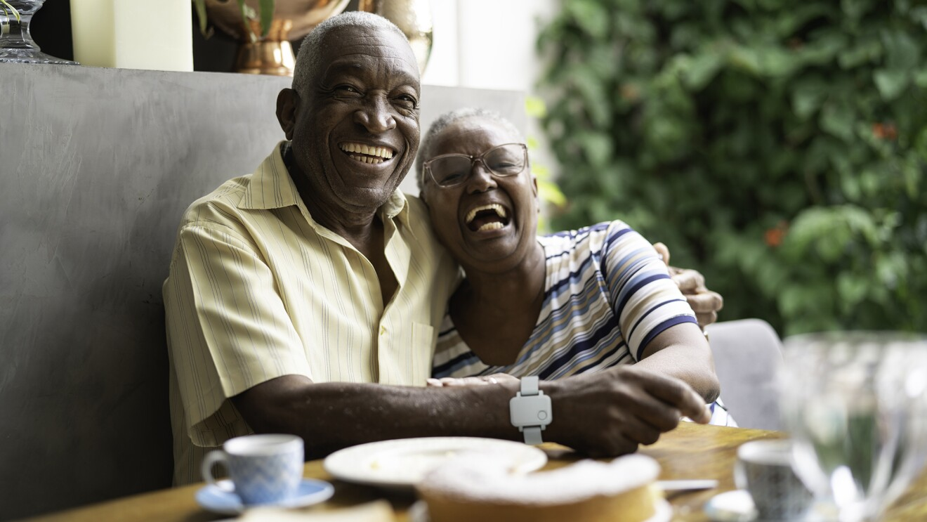 An image of a senior couple sitting in a booth at a table hugging each other and smiling.