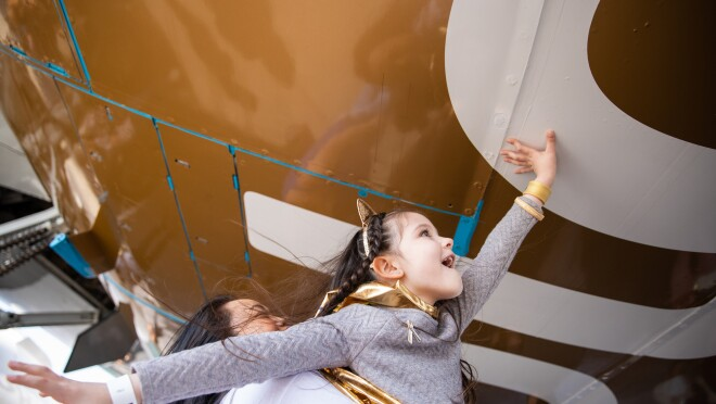 "A young girl wearing a gold cape, gold cat ears, and braids in her hair, reaches up (with help from a woman) to touch the bottom of a Prime Air aircraft with ""Go Gold"" messaging."