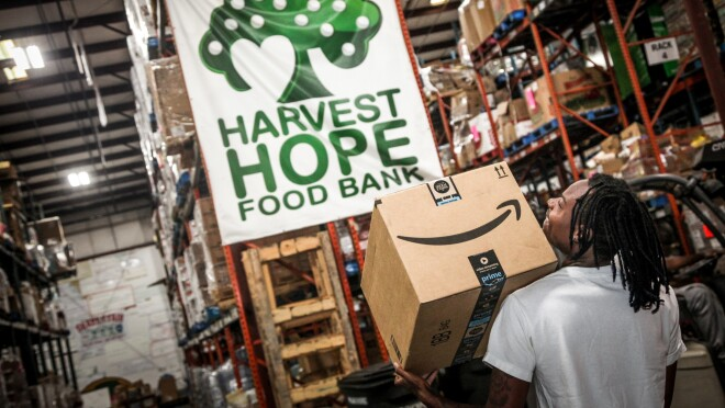 """A man walks through a warehouse space under a banner marked """"Harvest Hope Food Bank."""" He carries an Amazon box."""