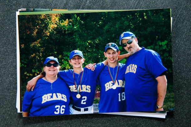 "A family of four wearing softball uniforms adorned with the word ""Bears."""
