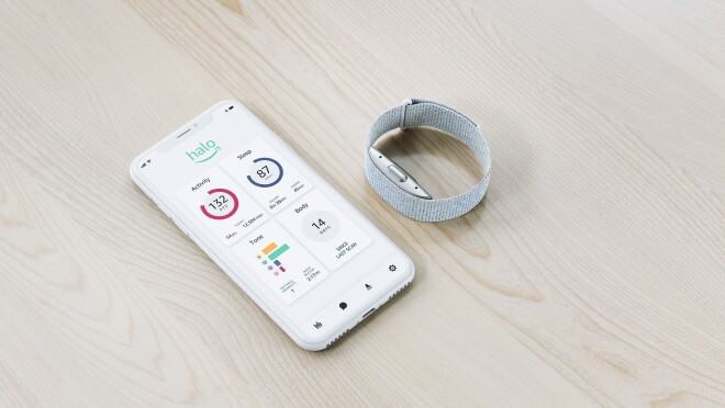 Amazon Halo band next to a mobile phone showing the Halo app experience, both rest on a wooden surface.