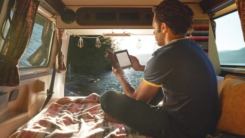 A man reading from a Kindle Paperwhite sits in the back of a camper van, in front of a large body of water.