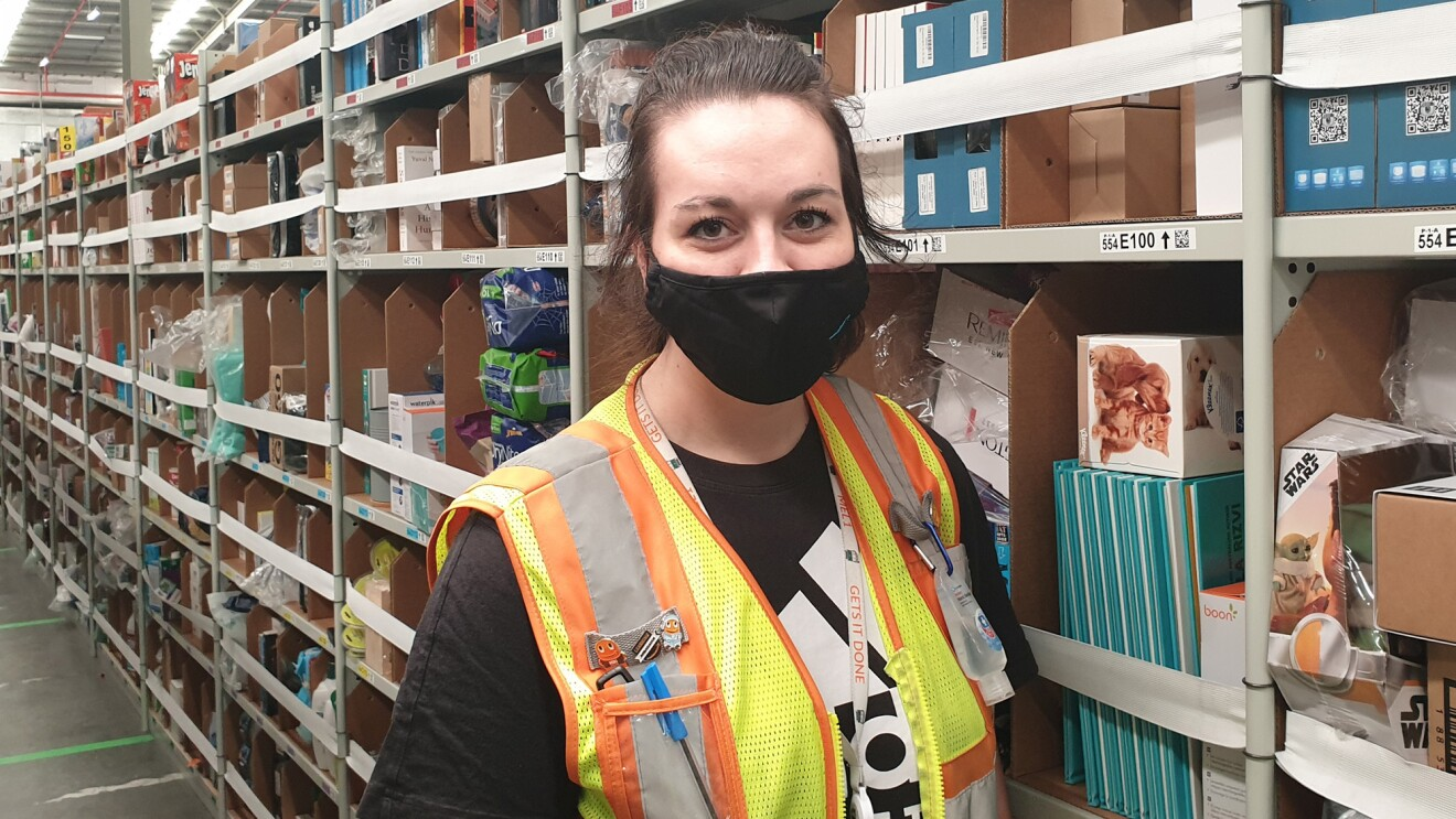 A woman wearing a black face mask and a yellow safety vest stands in an Amazon fulfillment center and looks at the camera.