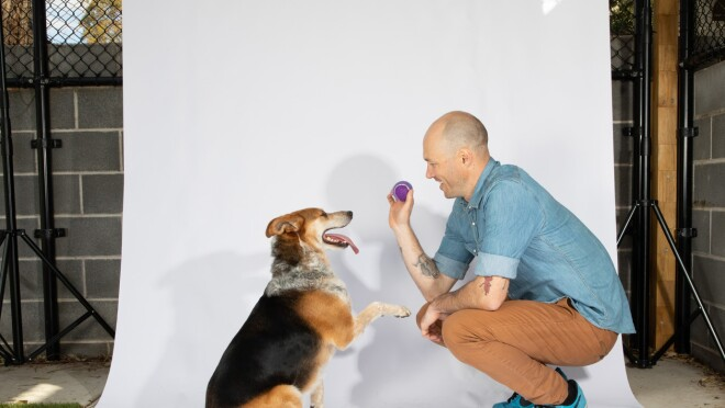 A man wearing a denim shirt, khakis, and tennis shoes crouches down, and holds a ball, in front of a dog with a paw extended and his tongue hanging out. They are on a white backdrop.