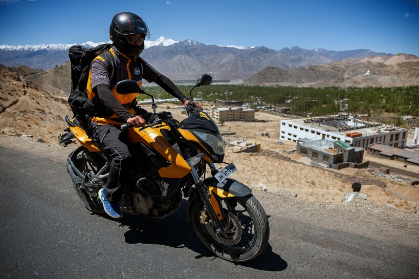 A helmeted motorcyclist wearing a large black backpack rides along an asphalt road. Buildings and snow-capped mountains are in the background of the image.