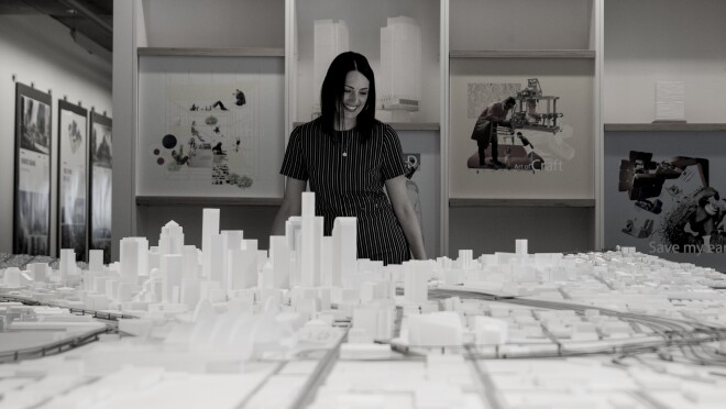 A woman in a grey-striped shirt stands over a large, scale model of downtown Seattle, looking down at the model.
