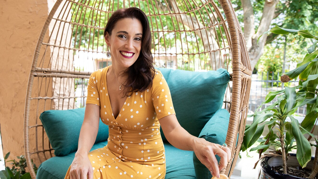 An image of a woman sitting in a wicker chair outside while smiling for a photo in a yello dress with white polka dots. The decor around her is colorful.