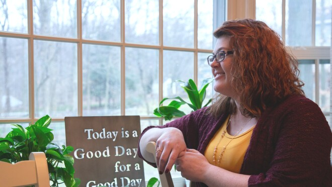 "A woman is photographed in profile standing next to a window. Near her is a sign that says ""Today is a Good Day for a Good Day."""