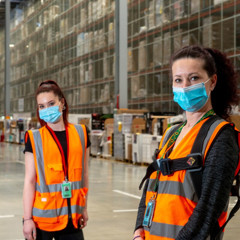 Two women, standing inside an Amazon fulfilment centre, wear orange safety vests and masks while looking at the camera.