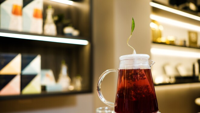 Tea steeps in a small glass pitcher adorned with a green leaf on top. The pitcher sits atop a larger pitcher filled with ice.