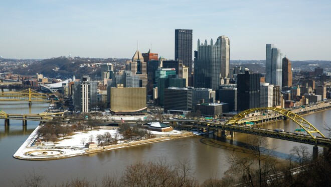 A park at the intersection of three rivers in Pittsburgh, PA. The tallest skyscraper says UPMC. There is snow on the ground and the sky is clear.