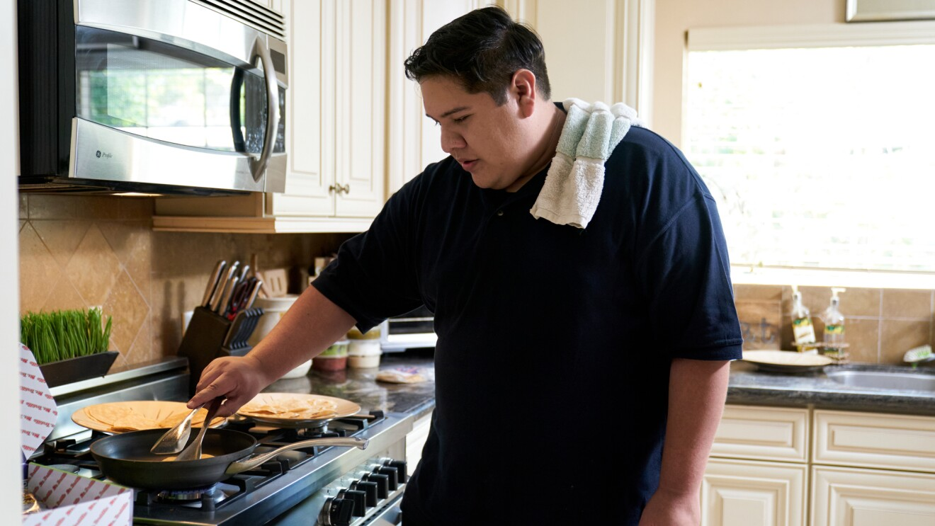 A man holding tongs cooks tortillas on a skillet.
